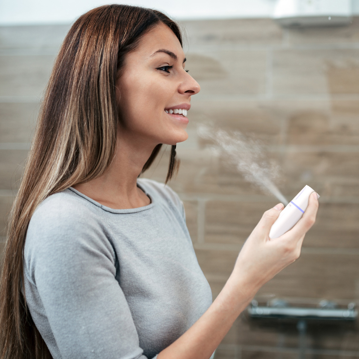 Smiling young woman applying make-up in the bathroom, side view.